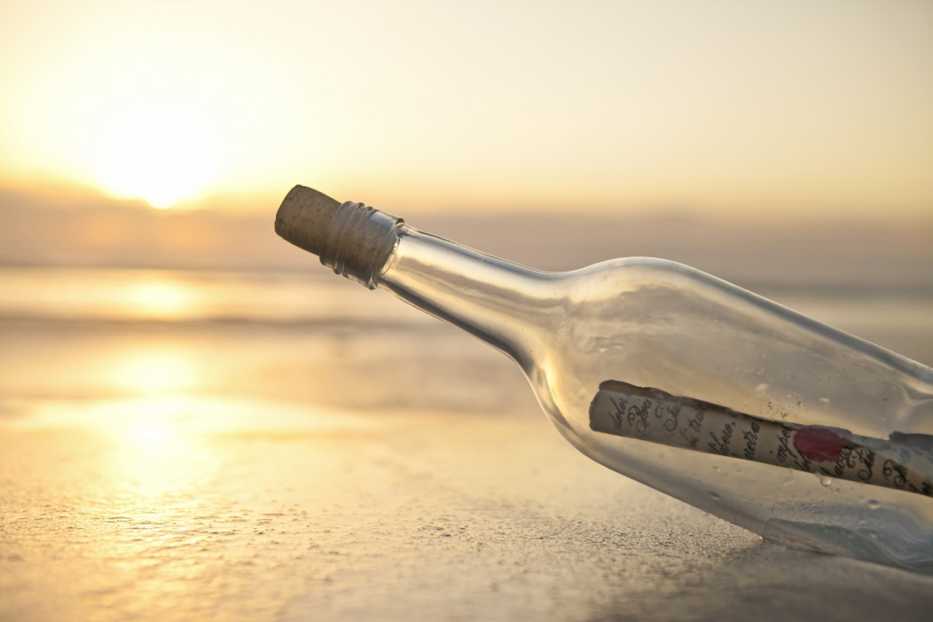 Message in a bottle on a beach and a beautiful sunset. Background is defocused.