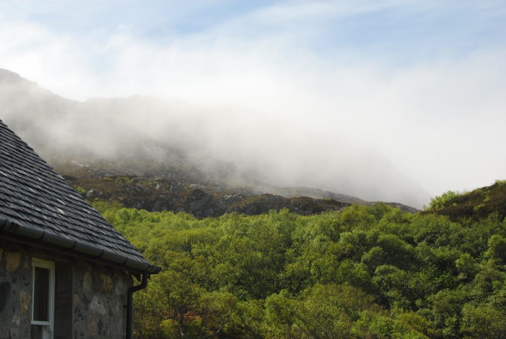 The mist rolls down from the high hills over the greenery towards the sea on Rona, Scotland.
