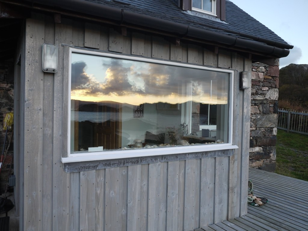 Reflection of the Hebridian Sea on the window of a cottage on Rona, Scotland.