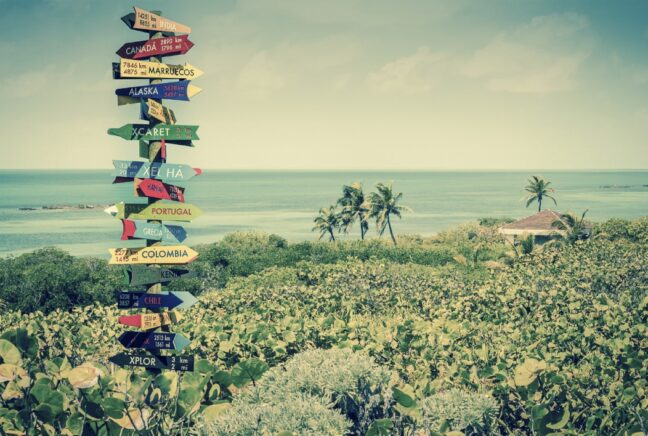 Travel Signpost with many arrows pointing in different directions. Background is a beautiful ocean and beach. Photo with vintage edges.
