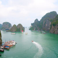 Travel to Vietnam's Halong Bay, a beautiful emerld green water bay surrounded by tall limestone islets covered with thick, green vegetation.