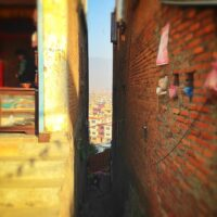 A beautiful photo of two buildings. The small gap between them reveals the sprawling city of Kathmandu, Nepal in the distance. This is the cover photo of the article: Cost of Living in Nepal