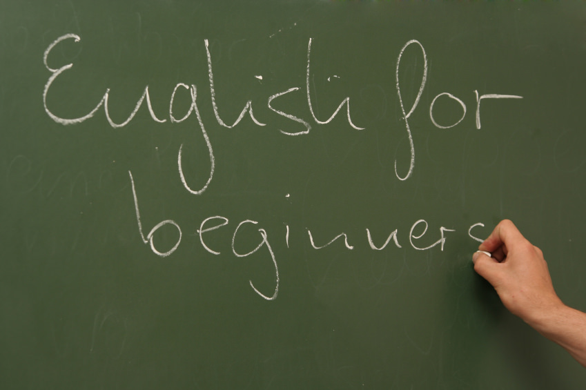 "A blackboard with a hand writing with a chalk. ""English for Beginners"" is written on the board. In the context of this article, it is quite obviously an ESL teacher teaching english abroad."