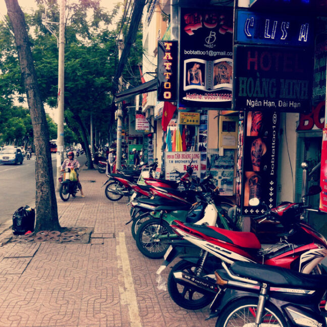 A street of Ho Chi Minh City, rows of motorbikes are parked outside modern-looking shops.