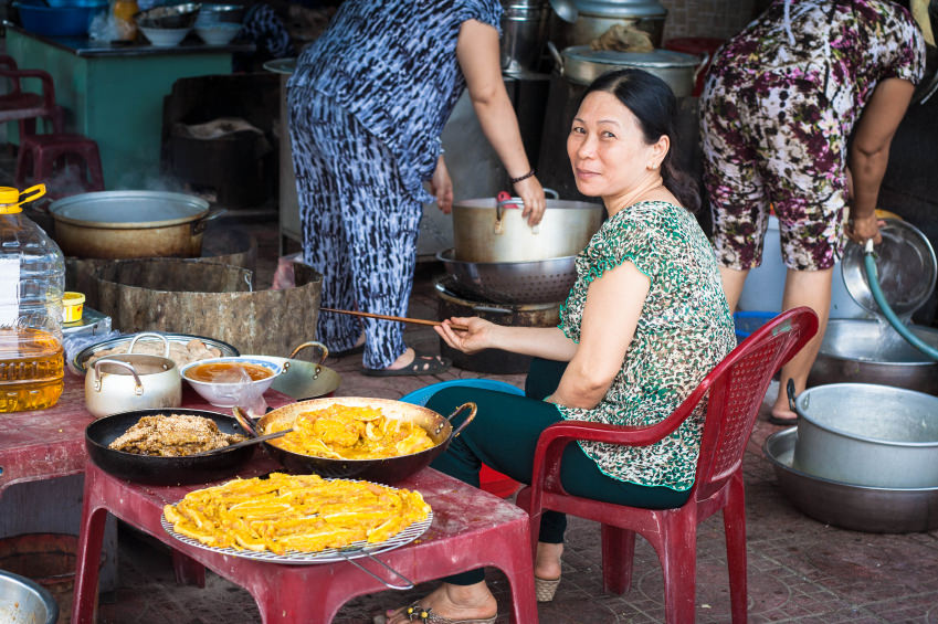 Title photo of the cost breakdown of living in Vietnam: a middle-aged Vietnamese woman sitting next to exotic dishes of food, which she has for sale.