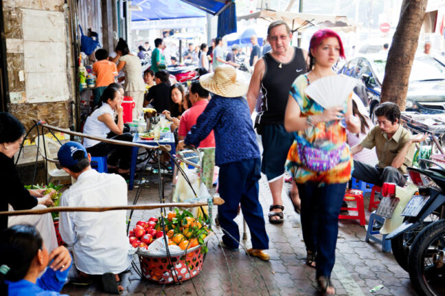 A typical bustling street of Saigon. A young white woman walks ahead of an older white male. Vietnamese are wheeling and dealing everywhere around them on the street. This lack of personal space and crowd is something expats must get used to when living in Vietnam.