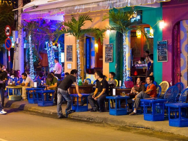 A bar at night in Ho Chi Minh City. Patrons are crowded outside, sitting in blue chairs, talking and drinking.