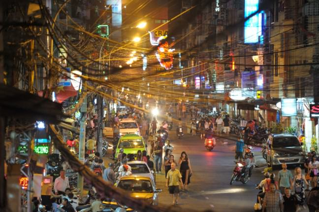 A night photo of the backpacker area in Saigon's District 1. The place is jam-packed and there are overhead electric wires everywhere.