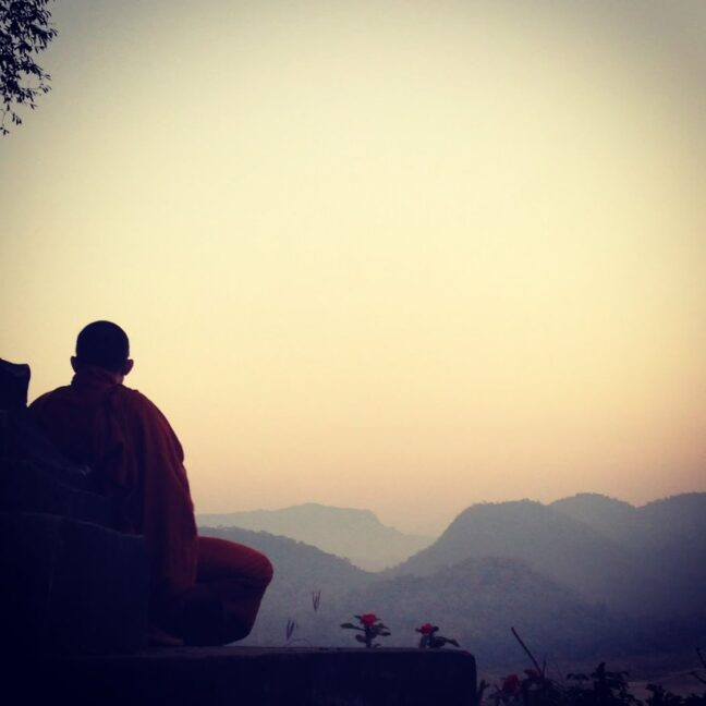 Atmospheric picture taken by the solo female traveler of a Nepali monk looking over a vast scenery of mountains at sunset.