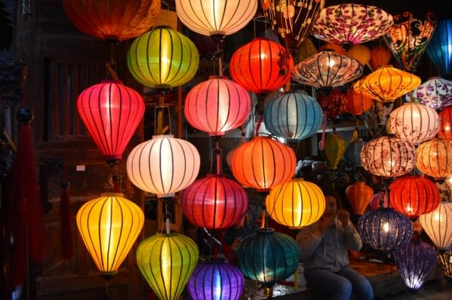 A picture of a myriad paper multi-colored lanterns at night. They are all mostly oval in shape, some round.