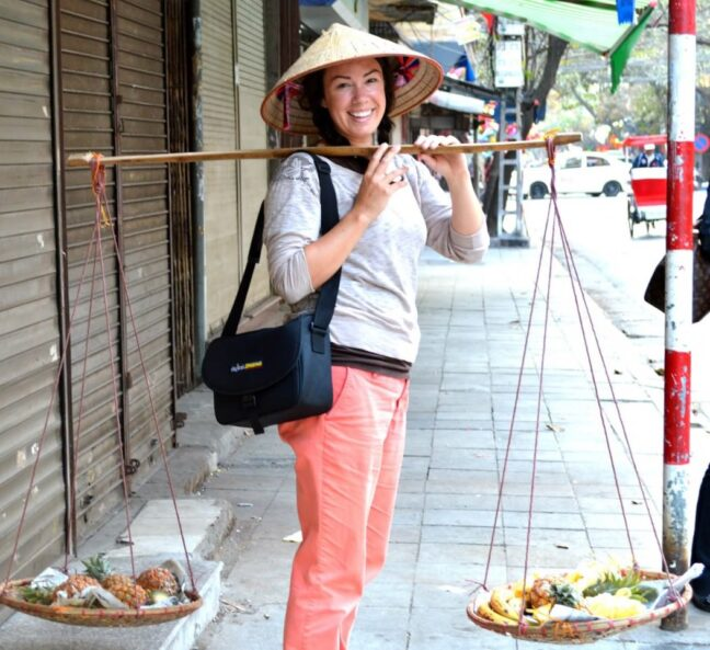 Rebecca dressed as a Vietnamese with a round tradition straw hat and carrying food with a Vietnamese shoulder balance