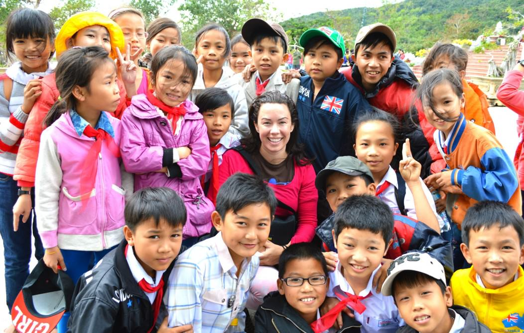 Solo Female Traveler Rebecca Voss having her photo taken and surrounded by over a dozen Asian children