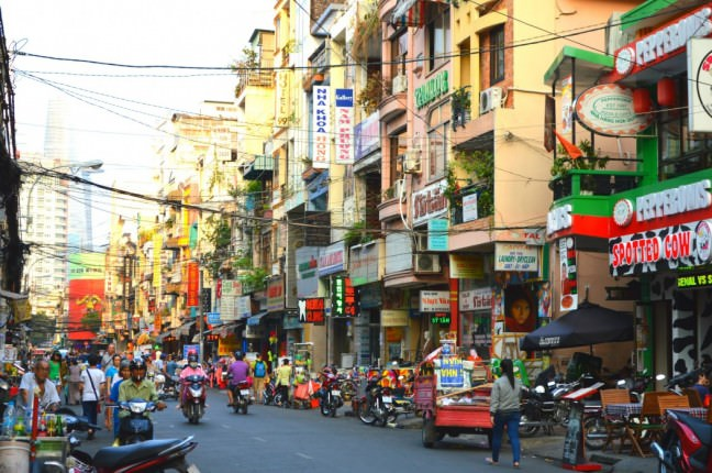 A solo female travel adventure down one of the busy, yet beautiful streets of Ho Chi Minh City. The buildings look colorful, but the street hectic, with merchants selling fruits and vegetables on the sidewalk.