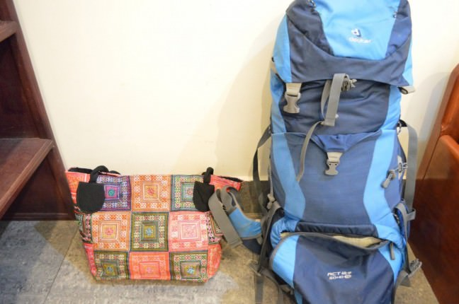 Solo female travel essentials: her blue backpack and an orange purse