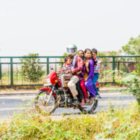 A family of five riding on a single bike in India