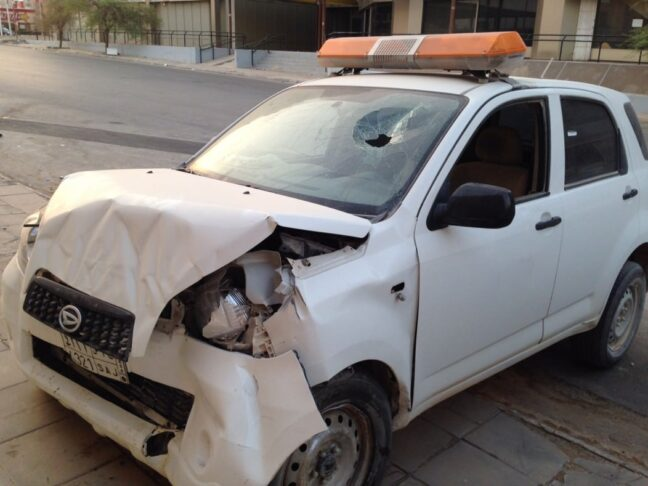 A Saudi insurance car that's been in an accident, smashed in the front.