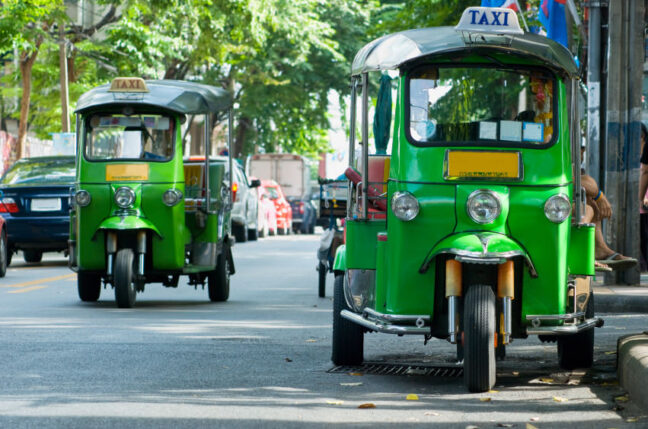 Two green tuk-tuk taxis in Bangkok. Shallow depth of field with the nearest taxi in focus.