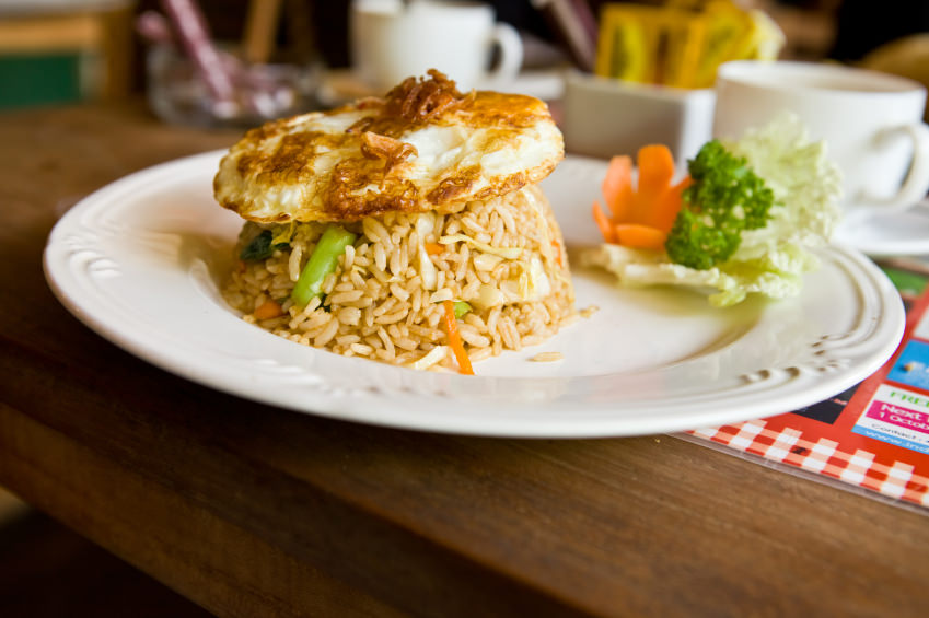 A dish of Indonesian nasi goreng, which is a spicy, fried rice dish with an egg on top and some chopped vegetables mixed in.