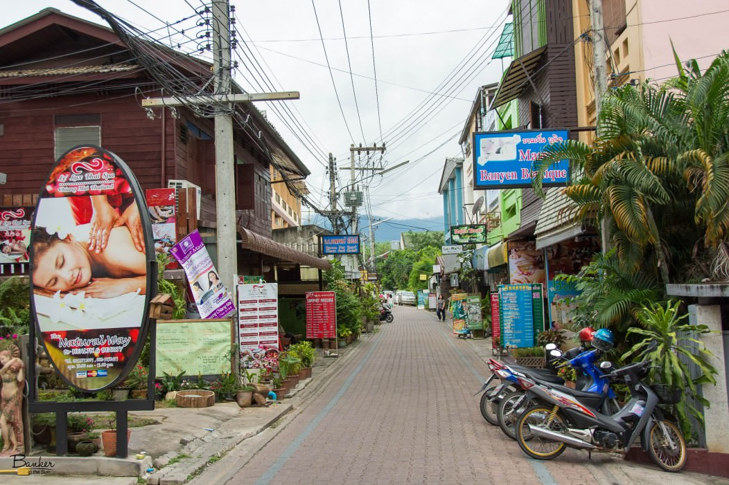 A quaint street in Chiang Mai, Thailand, with mountains in the background.