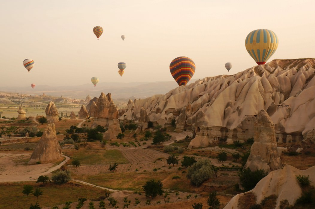A picture of hot air balloons hovering over the fairy chimneys in Cappadocia, Turkey.