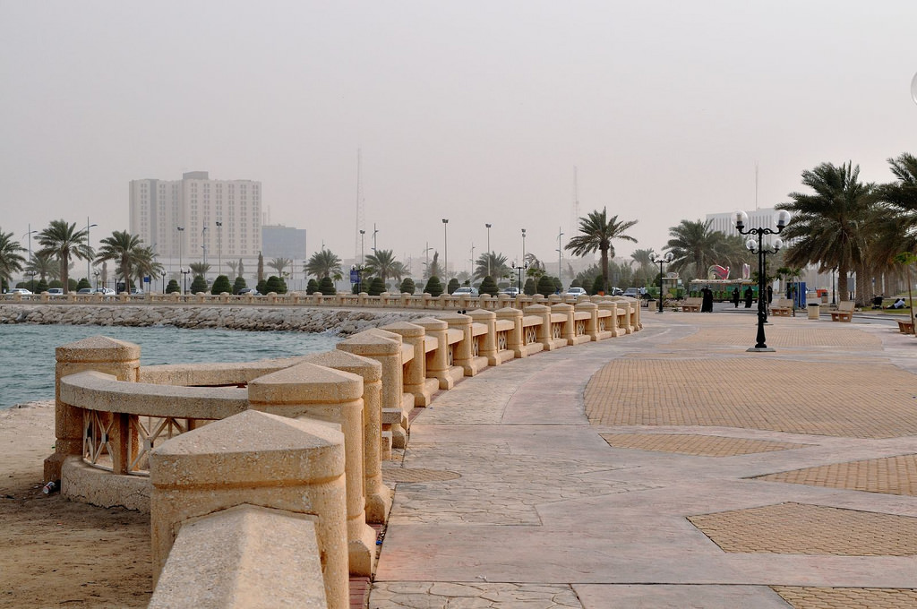 The Al Khobar-Dammam waterfront in Saudi Arabia. The signature haze is heavy in the air. The waterfront consists of rocks with a safety rail running the edge of the road.