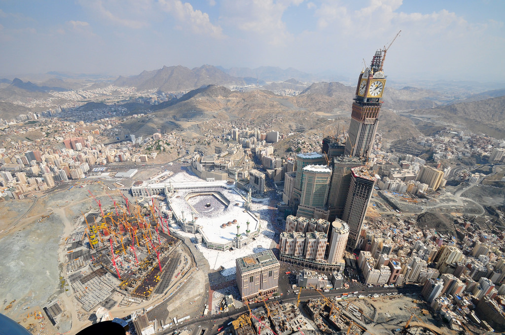 A picture of Mecca, Saudi Arabia, with the Hejaz mountains in the background. The Abraj Al Bait building towers over the city and the Masjid Al Haram, home to the Islamic religion. The skies look clear and city sprawls around the valley.