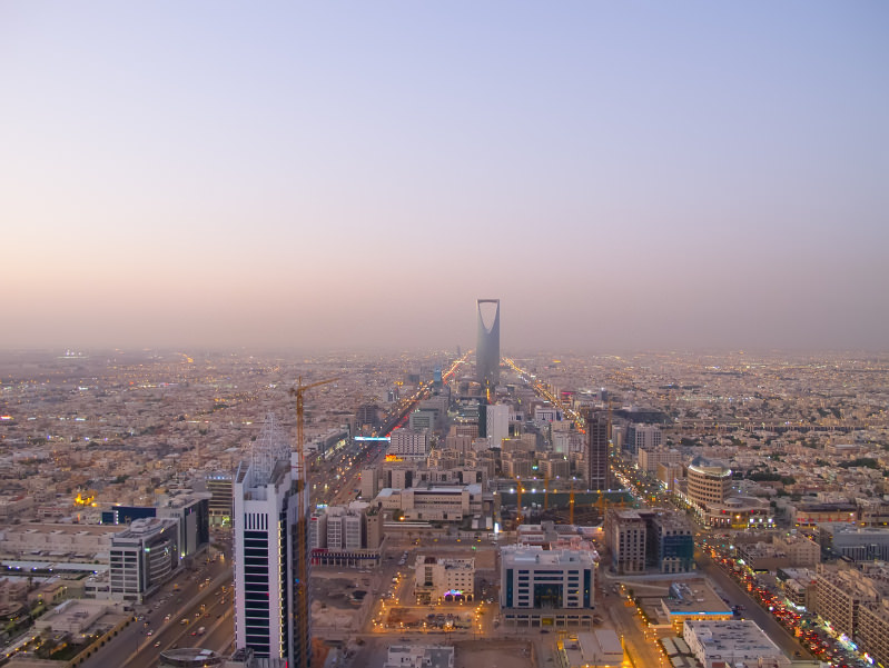 A panoramic picture of Riyadh's skyline; one of the best cities in Saudi Arabia, and by far the largest. The sky is hazy, the building look yellow and rather bland, and the ultra-modern kingdom tower rises up from the city center.