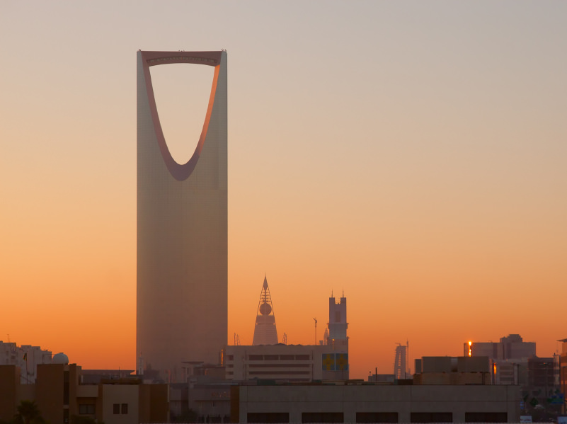 A silhouette of the kingdom tower in Riyadh, Saudi Arabia. The sky is at twilight dusk and a few buildings are silhouetted in the background.