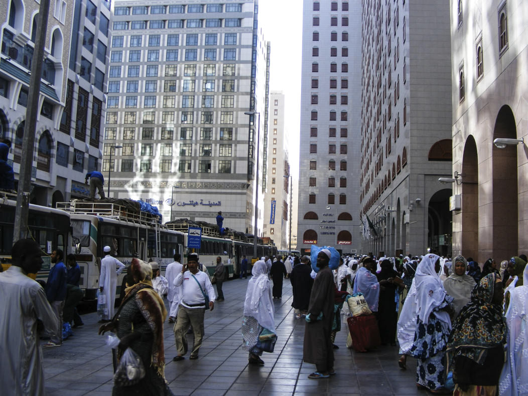 The streets of Medina, Saudi Arabia look modern in the downtown area. Tall buiildings line the street; women are dressed in veils and men in pilgrim clothes.