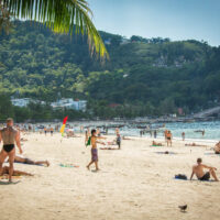 Patong Beach in Phuket Thailand. A great reason to be living in Phuket: a stretch of beach full of sunbathers, blue waters, and a lush hill rising in the background.