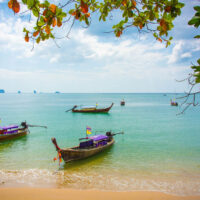 Longtail boats moored on beautiful Ao Nang Beach in Krabi province of Thailand. The water is light green and shallow, the sky blue. Beautiful living in Ao Nang Beach.