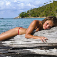 Picture of the Thai tropics and an expat girl in a small bikini laying on a log in the sea. Her expression is lonely.
