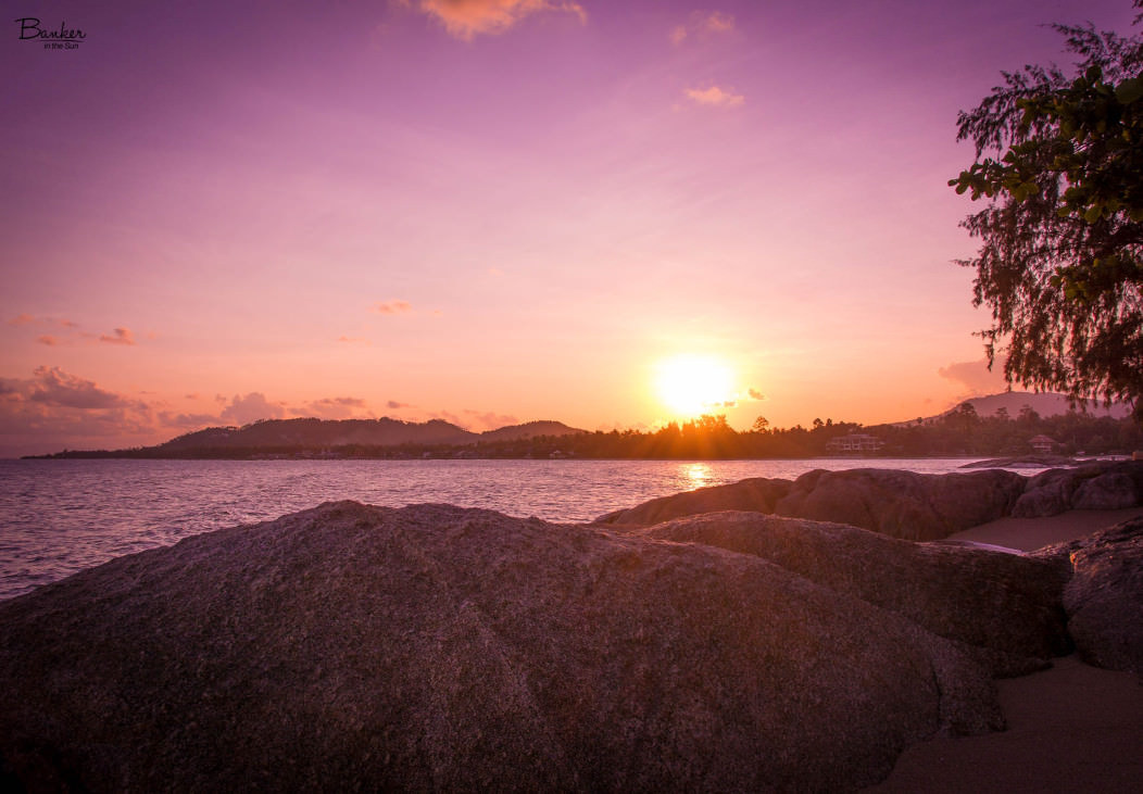 A beautiful sunset over Lamai Beach in Koh Samui, Thailand. The mountains are in the background and rocks on the beach in the foreground.