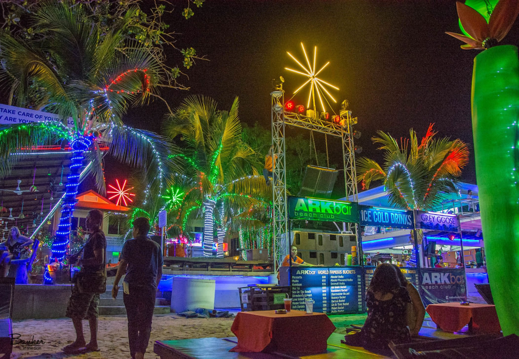 Arkbar Beach Club in Koh Samui, Thailand at night. Lots of different-colored neon lights and backpackers drinking beer on mattresses at the beach.