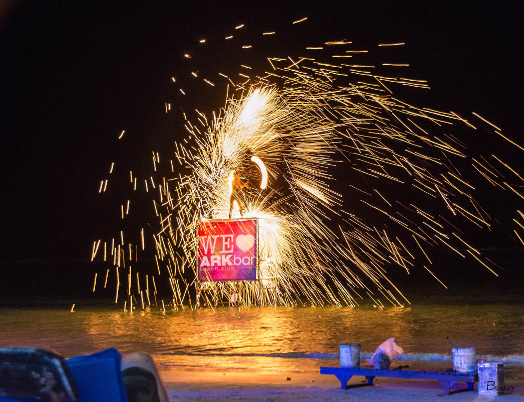 A fire show at Arkbar in Chaweng Beach, Koh Samui. A man is spinning fire around him on a pedestal set in the ocean.