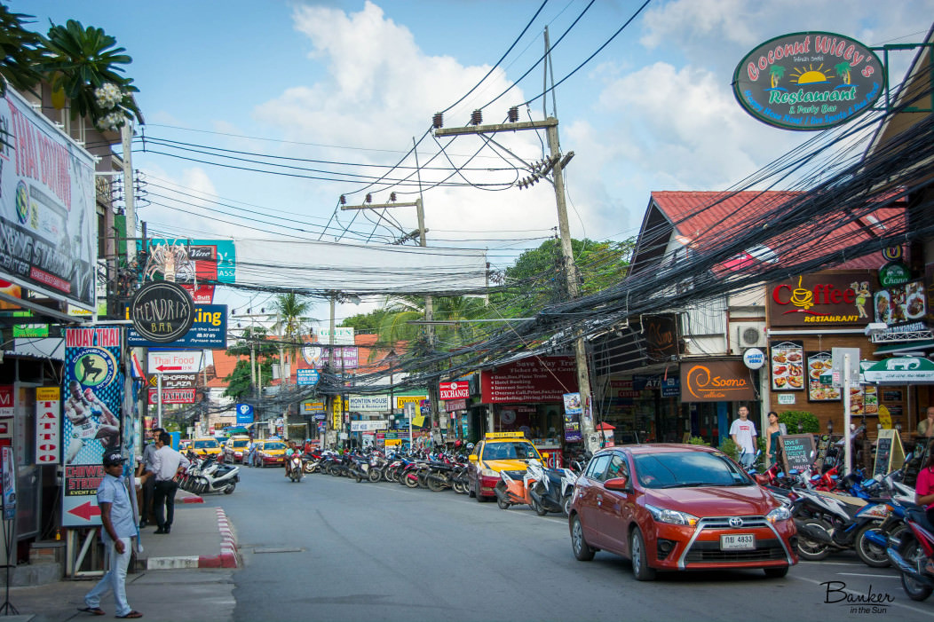 Chaweng Beach Street in Koh Samui, Thailand. Many motorcycles are parked along the sidewalk and overhead electric cables are numerous. The shops are very small and packed side by side.