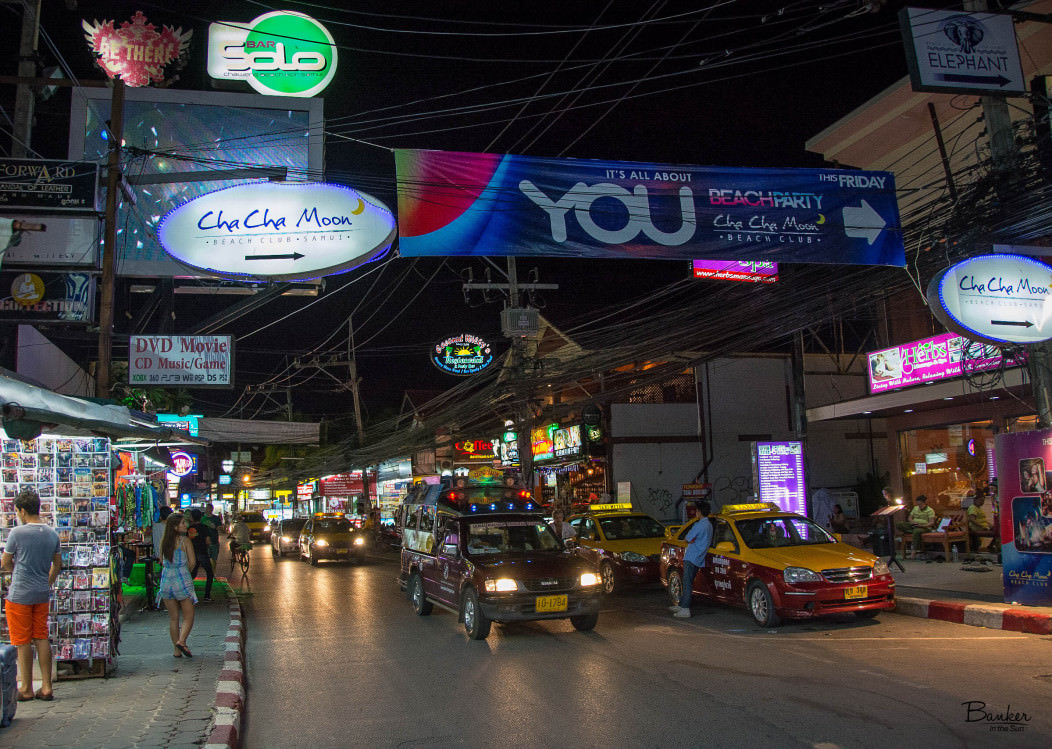 Chaweng Beach Street at Night. The neon shop signs are everywhere, and the sign for the Cha Cha Moon beach party is prominently displayed.