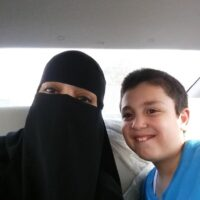 A picture of a veiled expat female living in Saudi Arabia in a car with a young Saudi student.