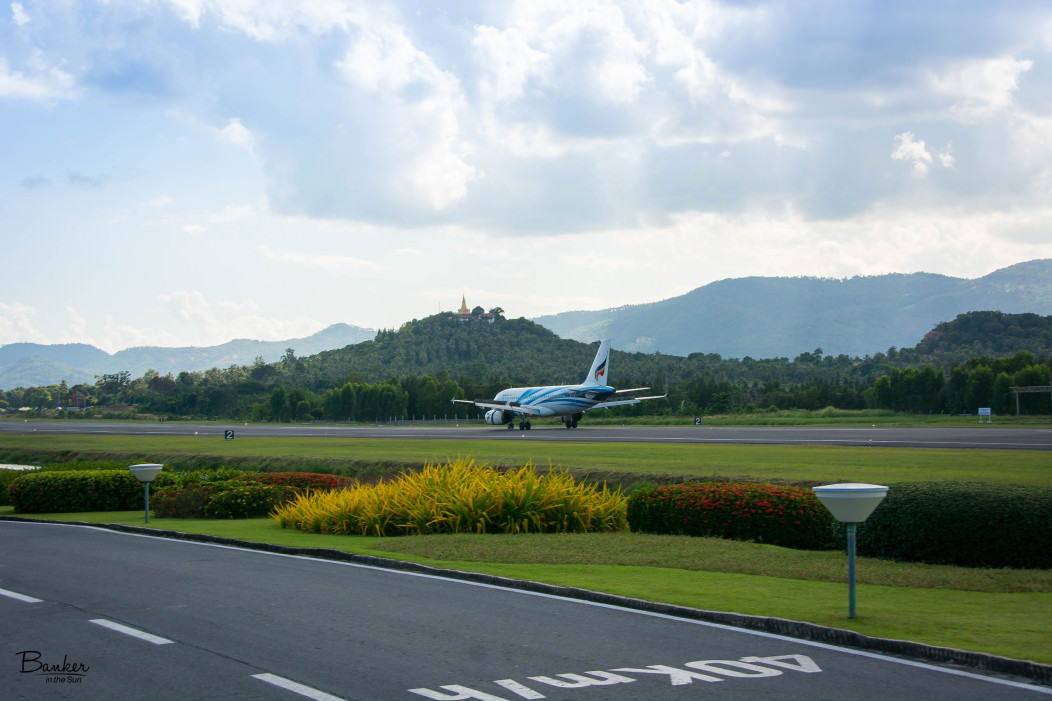 A Bangkok Airways plane landing at Koh Samui airport. In the distance on a mountain is Pagoda Khao Hua Jook. The scenery is tropical green and mountainous.