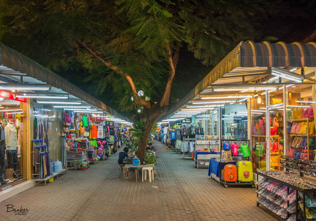 A traditional night market in Chaweng Beach, Thailand at night. It sells a variety of clothes, suitcases, and souvenirs.
