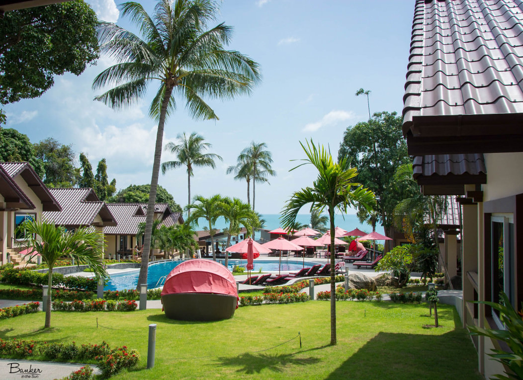 A picture of the Royal Beach Boutique Resort and Spa on Lamai Beach in Koh Samui, Thailand. It has a beautiful pool, many palm trees, and cabanas. It sits right on Lamai beach.