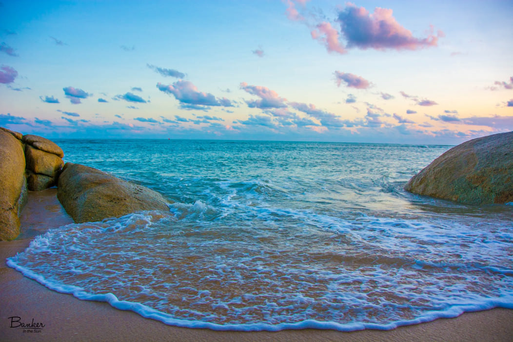 Sunset on Lamai Beach in Koh Samui, Thailand. The ocean water pulls right up to the camera.