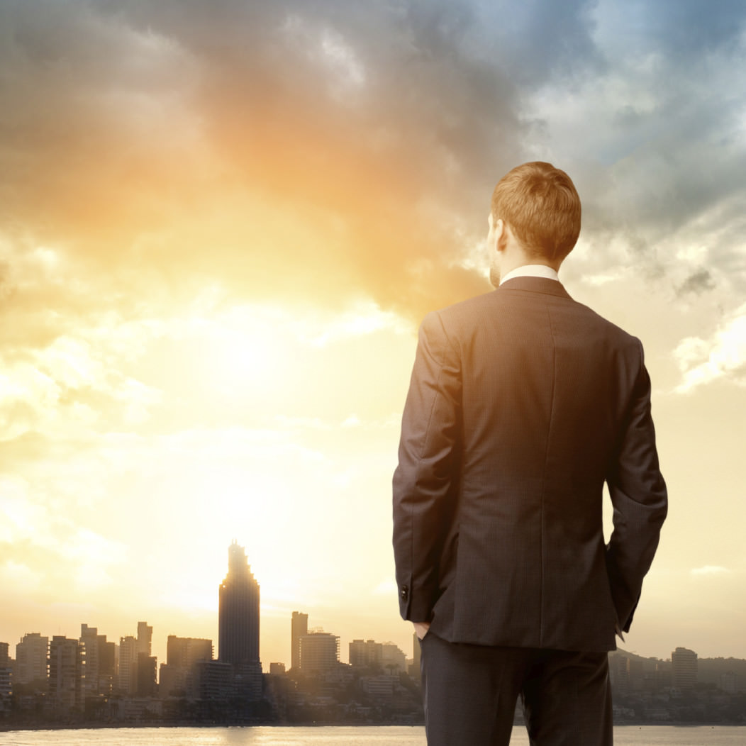Businessman gazing at a distant city skyline during a sunset. He seems to pondering the reasons to skip the job search.