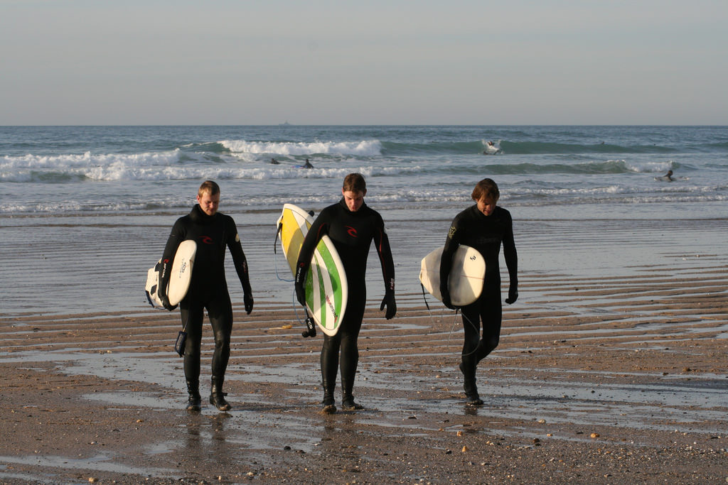 Three surfers walking with their boards along the sands of Newquay, one of the best surfing spots in the UK