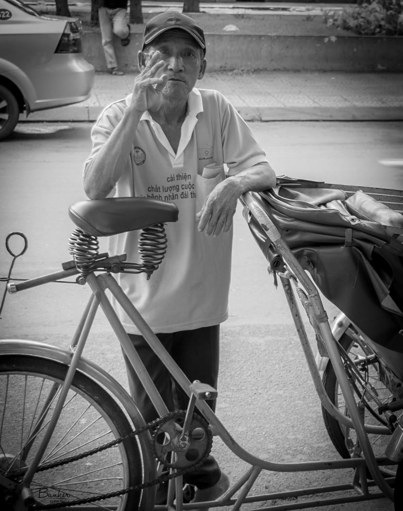 A black and white photo of a cyclos driver in Saigon (Ho Chi Minh City), Vietnam. He is leaning on his cyclo, smoking a cigarette, looking at the camera.