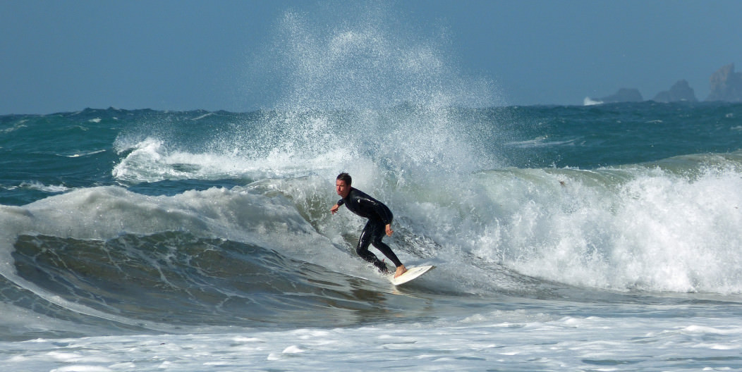 a surfer riding a wave in Boscombe, one of the best surf spots in the UK.