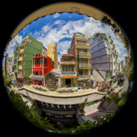 Picture of a silver ball with a reflection of the cheap accommodations in southeast Asia. The buildings are narrow, tall, and very colorful.