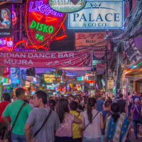 A very crowded Walking Street at night in Pattaya, Thailand. Tons of clubs, go-go bars, and restaurants line both sides of the streets. Bar girls and tourists crowd the neon-lit street.