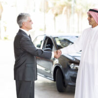A western businessman shaking a Saudi businessman's hand, demonstrationg proper business etiquette in Saudi Arabia.