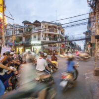 Motorcycle traffic during the evening in the beautiful district 1 of Ho Chi Minh City, Vietnam. The buildings possess a French architecture.
